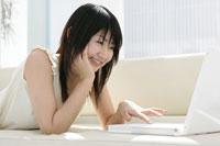 ソファでノートパソコンをする女性