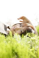 若草の上で寝転ぶ女性 11006002600| 写真素材・ストックフォト・画像・イラスト素材|アマナイメージズ