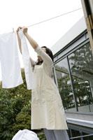 洗濯物を干すお母さん 11006002799| 写真素材・ストックフォト・画像・イラスト素材|アマナイメージズ
