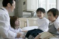 子供たちの診察をする男性医師と女性看護師