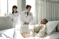 介護ベッドの男性患者と医師と女性看護師