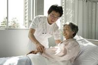 介護ベッドの女性患者と男性医師(研修医)