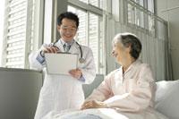 介護ベッドの女性患者と男性医師