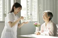 介護ベッドの女性患者と女性看護師