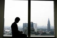 窓の側でパソコンをする男性のシルエット 11006003125| 写真素材・ストックフォト・画像・イラスト素材|アマナイメージズ