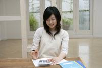 家計簿と女性 11006003633| 写真素材・ストックフォト・画像・イラスト素材|アマナイメージズ