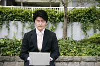 ベンチでパソコンをするビジネスマン