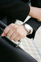 ビル街で腕時計を見るビジネスマン