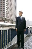 ビル街に立つシニアのビジネスマン