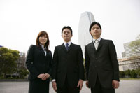 ビル街を背景に立つビジネスマン男女3人