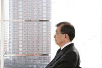 窓を背景に座るシニアのビジネスマン