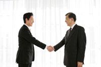 窓の近くで握手をするビジネスマン2人