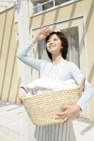 洗濯物を運ぶエプロン姿の女性