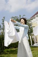 洗濯物を干すエプロン姿の女性