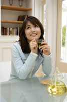 テーブルでお茶を飲む20代の女性
