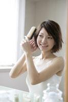 髪の毛を梳かす若い女性
