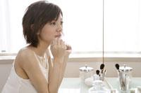 化粧台で化粧をする若い女性 11006004575| 写真素材・ストックフォト・画像・イラスト素材|アマナイメージズ