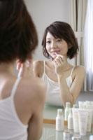 化粧台で化粧をする若い女性