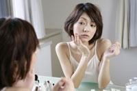 化粧台で化粧をする若い女性 11006004578| 写真素材・ストックフォト・画像・イラスト素材|アマナイメージズ