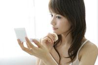 ソファで化粧をする若い女性 11006004613| 写真素材・ストックフォト・画像・イラスト素材|アマナイメージズ