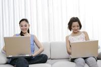 ソファでそれぞれノートパソコンを使う2人の若い女性