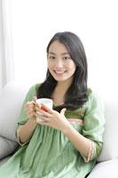 ソファでマグカップを持つ若い女性