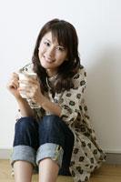 床に座ってマグカップを持つ若い女性