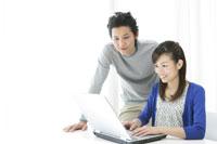 パソコンを使う若いカップル 11006008888| 写真素材・ストックフォト・画像・イラスト素材|アマナイメージズ