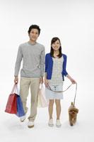買い物袋を持つ若いカップルと犬
