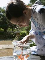 金魚鉢を覗き込む女性
