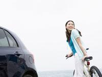 自転車に寄り掛かる女性