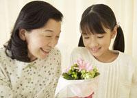 花束を見つめる祖母と孫