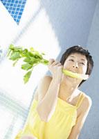 セロリを食べる女性 11007057552| 写真素材・ストックフォト・画像・イラスト素材|アマナイメージズ