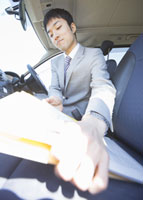 車内で書類をまとめるビジネスマン 11007058174| 写真素材・ストックフォト・画像・イラスト素材|アマナイメージズ