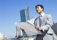 図面を広げるビジネスマン