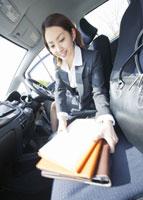 車内で書類をまとめるビジネスウーマン