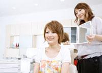 鏡を持つ美容師と若い女性