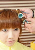 髪にロットを巻かれる若い女性
