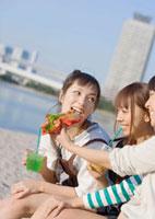 海岸でホットドックを食べる女性