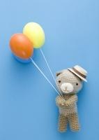 風船を持つクマの編みぐるみ