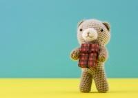 プレゼントを持つクマの編みぐるみ