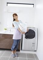 洗濯かごを抱えるミドル女性