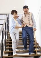 階段を下りるシニア夫婦