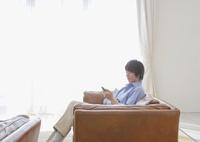 ソファに座ってスマートフォンを操作するミドル男性