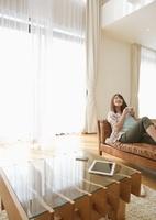 ソファに座ってコーヒーを飲むミドル女性