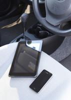 運転席のシートに置かれたタブレットPCとスマートフォン