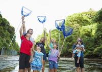 川の中で網を持って見上げる大家族