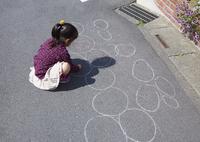 チョークでお絵描きする女の子