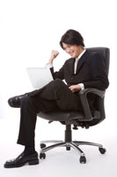 Businessman sitting with laptop on thigh
