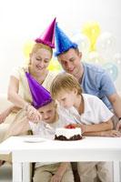 Portait of family cutting birthday cake